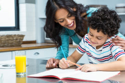 adult woman helping child with homework at table with glass of orange juice