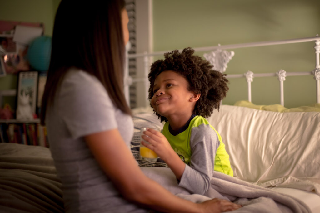 boy smiling and drinking orange juice in bed while mom sits with him