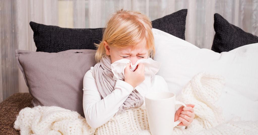 little girl sneezing into tissue