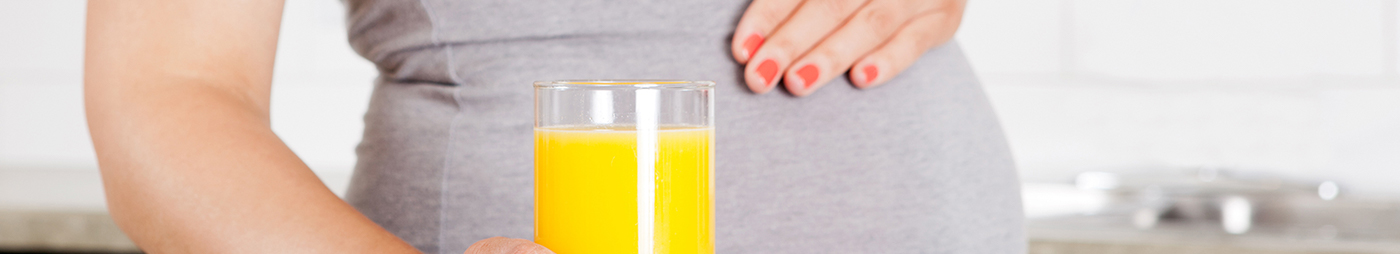 pregnant woman holding a glass of florida orange juice which is a good source of folate