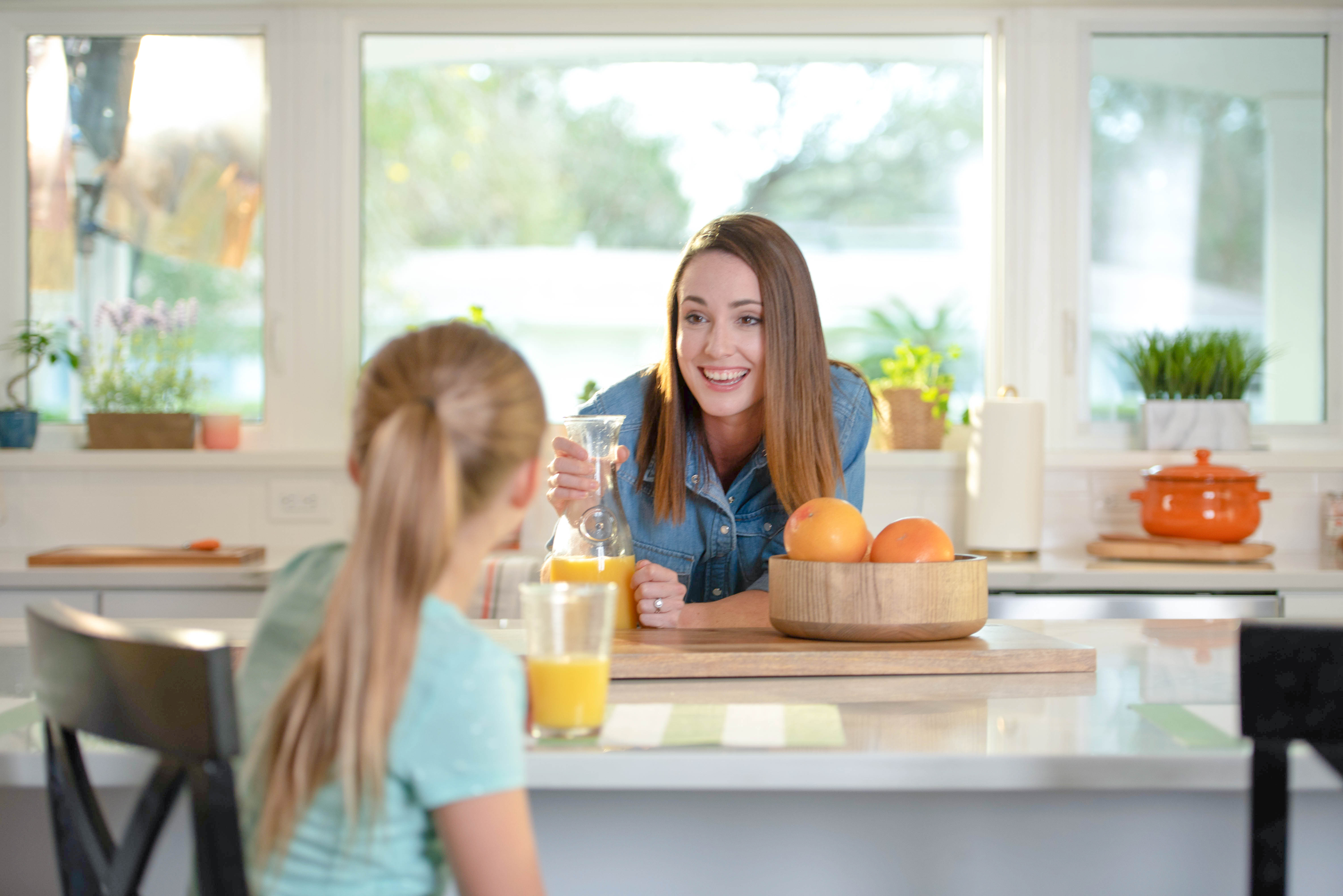 Mom and little girl sitting at a counter drinking florida orange juice