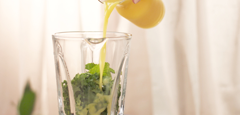 pouring florida orange juice into a blender with kale