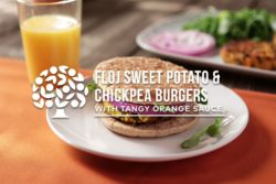 floj sweet potato chickpea burger on plate next to glass of orange juice
