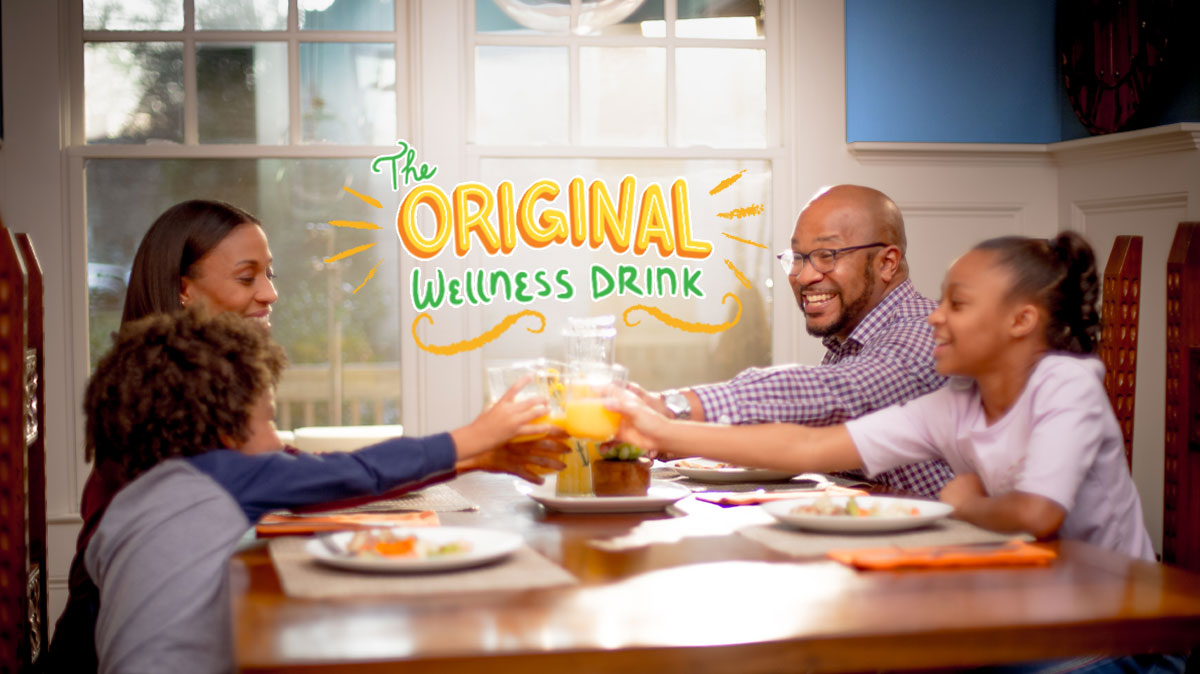 """family sitting together at table eating and drinking orange juice with """"the originial wellness drink"""" in text"""